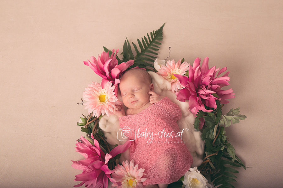 Neugeborenes in selbstgemachtem Blumenkranz während dem Neugeborenenshooting